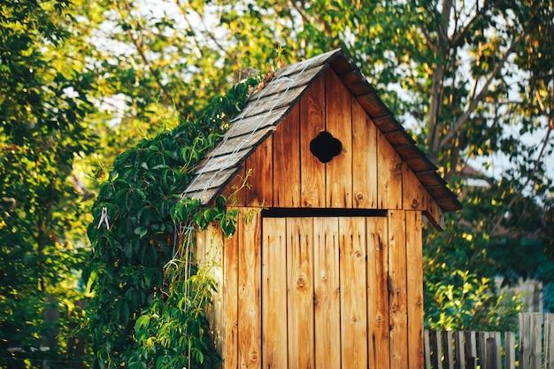 Toilette rurale in legno nella boscaglia, bagno pubblico
