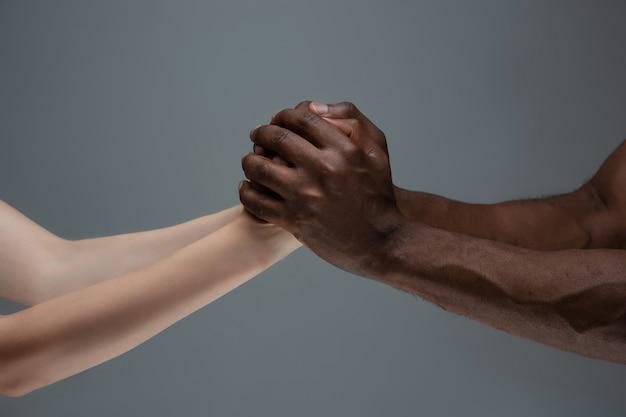Tolleranza razziale. rispetta l'unità sociale. gesturing africano e caucasico delle mani isolato su gray