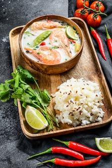 Tom kha gai. zuppa di cocco cremosa speziata con pollo e gamberi. cibo thailandese. superficie nera. vista dall'alto