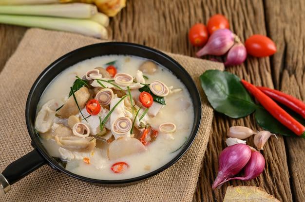 Tom kha kai in padella con foglie di lime kaffir, citronella, cipolla rossa, galanga e peperoncino.