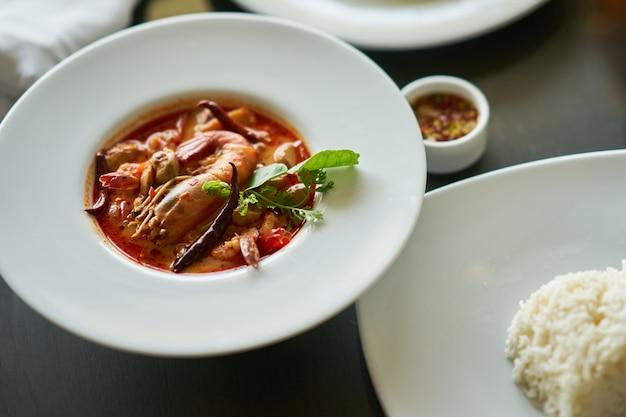 Tom yam kung con riso e salsa di pesce tuffo nel piatto famoso tradizionale tailandese