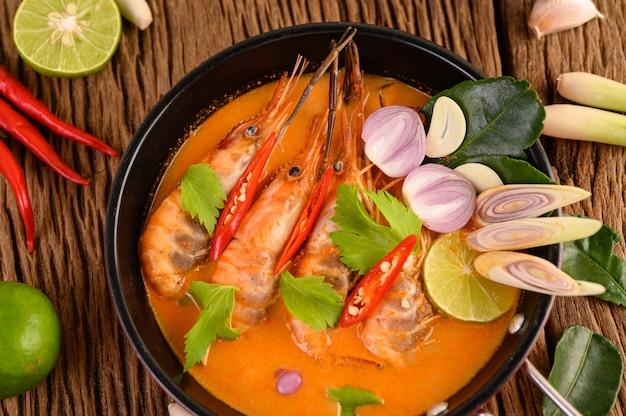 Tom yum kung thai piccante zuppa di gamberi con citronella, limone, galanga e peperoncino sul tavolo di legno, cibo in thailandia