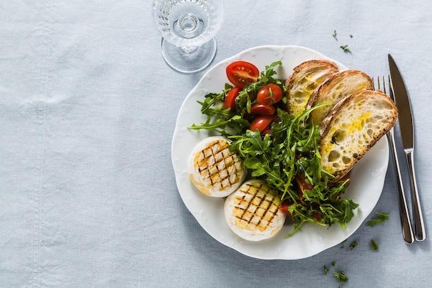 Tomino italiano alla griglia servito su un tavolo con insalata di rucola e pane fresco ciabatta fatta in casa e pomodoro su una tovaglia festiva di lino blu. menu estivo