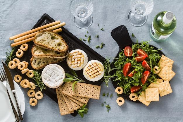 Tomino italiano alla griglia servito su un tavolo con vino bianco, crackers, grissini e taralli con erbe aromatiche e rucola e insalata di pomodori su una tovaglia festiva di lino blu. menu estivo
