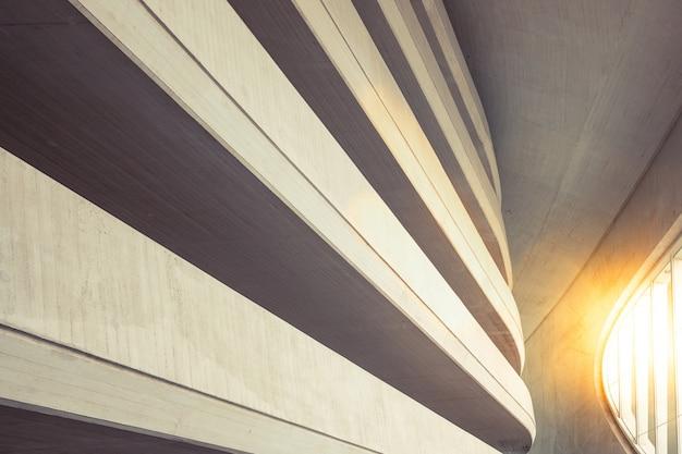 Toni caldi sullo sfondo degli interni di una costruzione minimalista di ruvide pareti e linee strutturate, illuminate da un raggio di sole al tramonto.