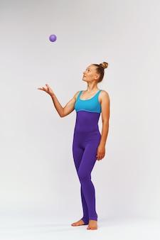 Tonica donna snella in abiti sportivi con una palla da massaggio in mano