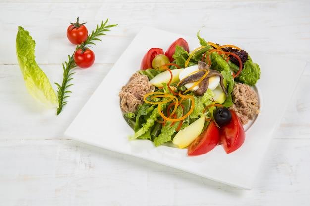 Tonno, acciughe, uova. stato verde, fette di peperone giallo dolce, cipolla rossa, olive nere e pomodori gustosa insalata sul piatto bianco