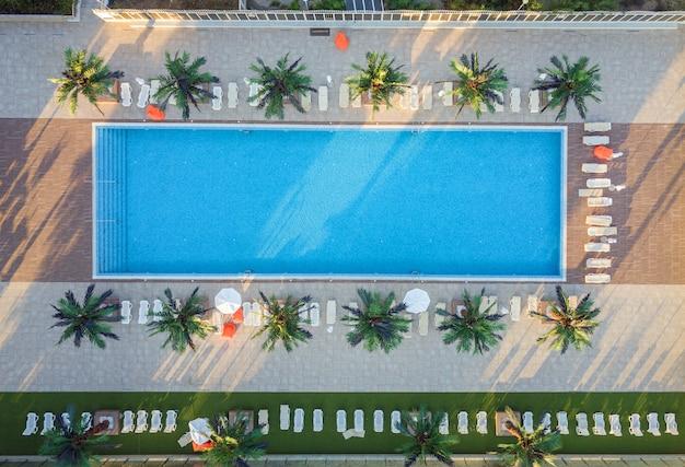 Top-down vista aerea della piscina dell'hotel con acqua cristallina circondata da palme e sdraio sdraiate nella località turistica vicino al mare nella calda stagione estiva.