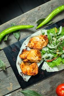 Top kebab di pollo servito con cipolle grigliate di pomodoro e pepe sul bordo nero