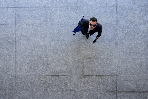 Top shot di uomo d'affari in tuta e occhiali da sole in piedi sul marciapiede