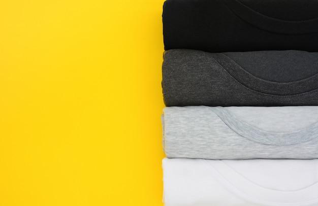 Top view stack di t-shirt nera, grigia e bianca arrotolata su giallo