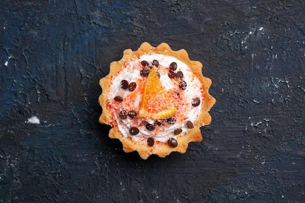 Top vista ravvicinata deliziosa torta con crema e fetta d'arancia sul biscotto di frutta torta superficie scura