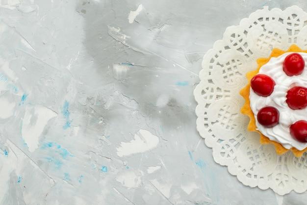 Top vista ravvicinata piccola deliziosa torta con crema e frutti rossi isolato sulla superficie chiara
