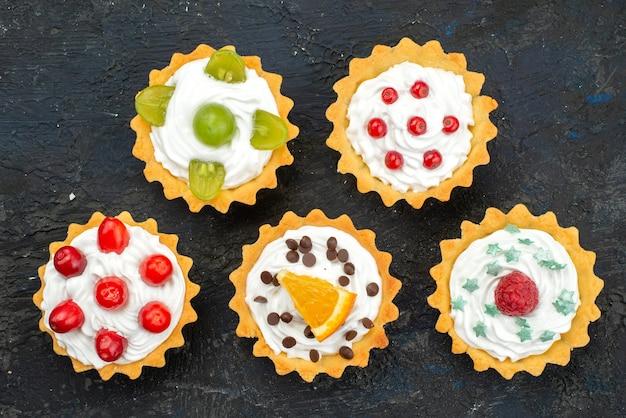 Top vista ravvicinata piccole deliziose torte con panna e frutta fresca sulla superficie scura dolce biscotto torta zucchero tè dessert