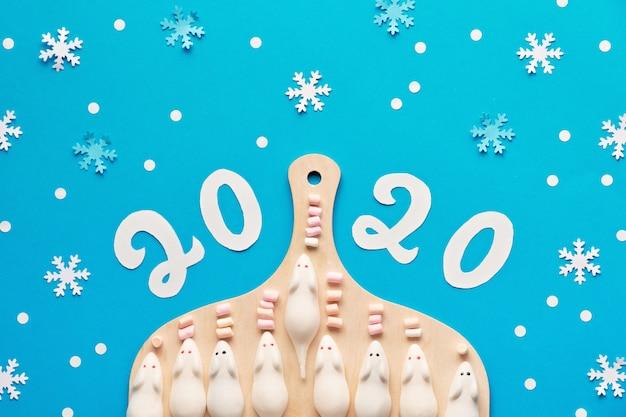 Topi bianchi dolci con il numero 2020 su carta pastello, capodanno