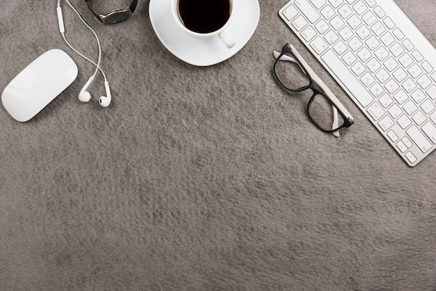 Topo; tastiera; tazza di caffè; auricolare; orologio da polso su sfondo grigio