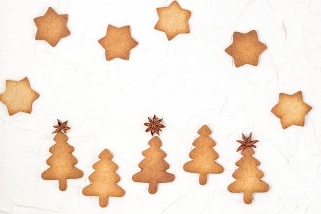 Toppers della stella dei biscotti dell'albero di natale su fondo bianco con copyspace.