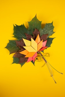 Topshot tradizionale caduto di origami di arte del mestiere di carta di concetto colorato caduto delle foglie su fondo giallo