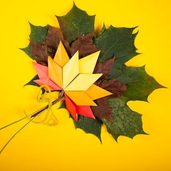 Topshot tradizionale di origami di arte del mestiere di carta del concetto di autunno fatto a mano caduto delle foglie su fondo giallo