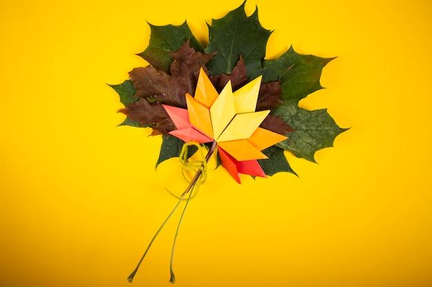 Topshot tradizionale di origami di arte del mestiere di carta di concetto di autunno delle foglie cadute sul papercraft giallo del fondo