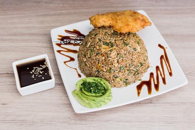 Torimeshi con pesce fritto, salsa di soia e avocado su un tavolo di legno