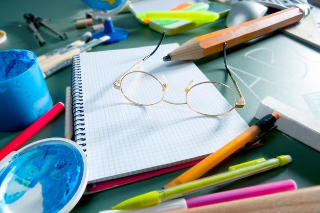 Torna a scuola ancora sulla lavagna, occhiali, matita, vernice