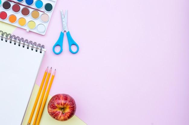 Torna a scuola composizione con copia spazio a destra su sfondo rosa e giallo