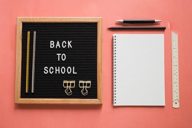 Torna a scuola testo su ardesia con le cartolerie su sfondo colorato