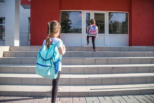 Torna al concetto di educazione scolastica con ragazzine, studenti elementari, portando zaini andando a lezione