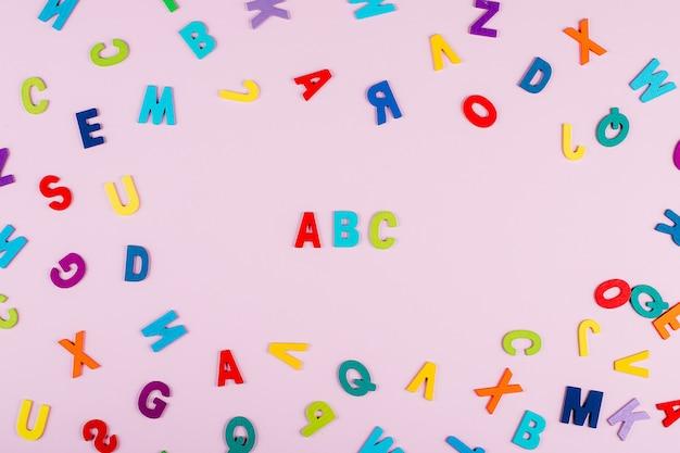 Torna al concetto di scuola. alfabeto luminoso e multicolore. lettere in legno colorate su
