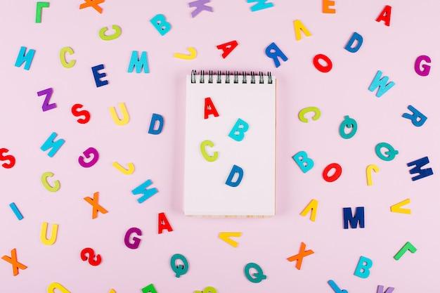 Torna al concetto di scuola. alfabeto multicolore luminoso lettere in legno colorate su rosa