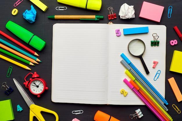 Torna al concetto di scuola con diverse forniture per ufficio con il diario sulla tavola di legno
