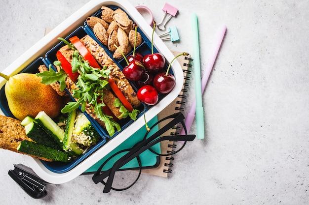 Torna al concetto di scuola con scatola di pranzo con sandwich, frutta, snack, notebook