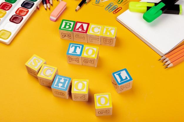 Torna al concetto di scuola. cubi alfabetici in legno colorati su giallo brillante