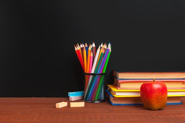 Torna al concetto di scuola. lavagna con i libri e la mela sullo scrittorio di legno