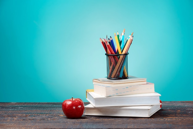 Torna al concetto di scuola. libri, matite colorate e mela