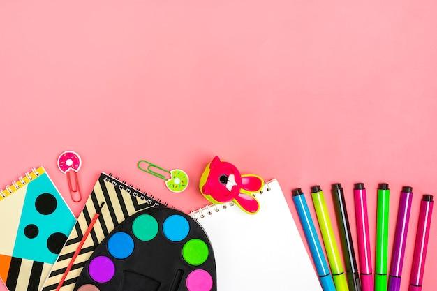 Torna al concetto di scuola. materiale scolastico su rosa, piatto laico.