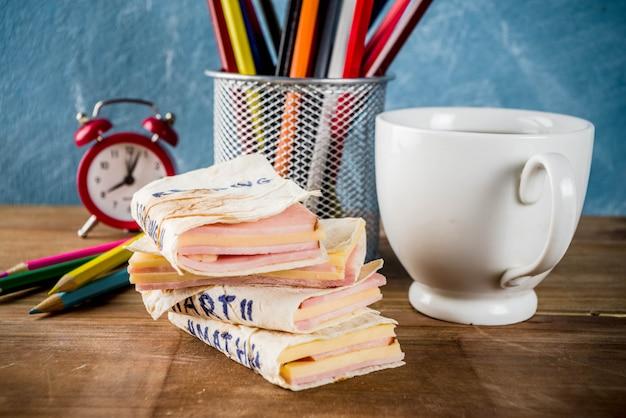 Torna al concetto di scuola, panini scolastici creativi per colazione o pranzo, con formaggio e prosciutto