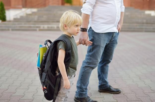 Torna al concetto di scuola. piccolo allievo con suo padre. primo giorno di scuola elementare.