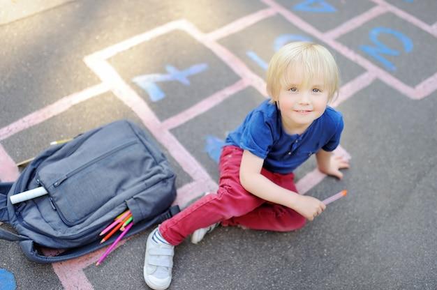 Torna al concetto di scuola. ragazzino sul cortile della scuola