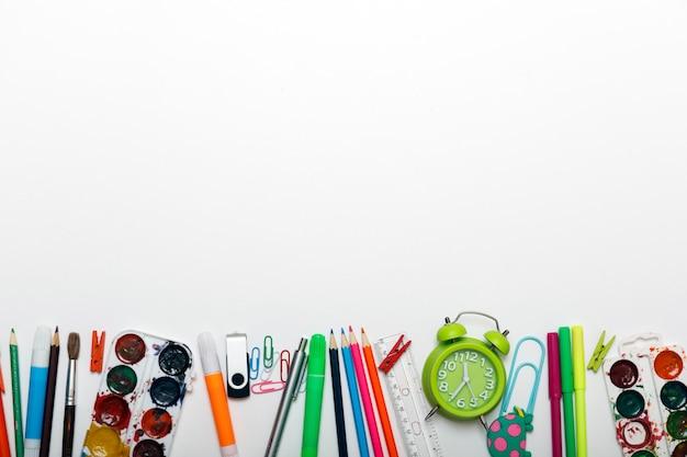 Torna al concetto di scuola. sveglia, vernice, matite e forbici