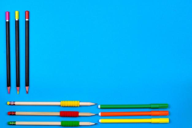 Torna al concetto di scuola: telaio con matite colorate e pastelli su sfondo blu