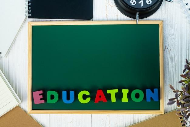 Torna al concetto di scuola, testo di educazione e lavagna verde con un mucchio di carta notebook, articoli di cancelleria o materiale scolastico.