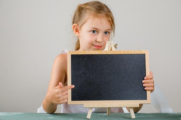 Torna al concetto di scuola vista laterale. bambina che tiene e che mostra lavagna.