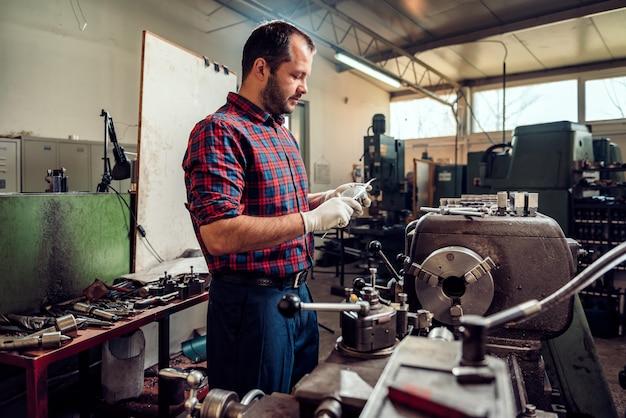 Tornitore del lavoratore del metallo facendo uso del calibro dalla macchina del tornio