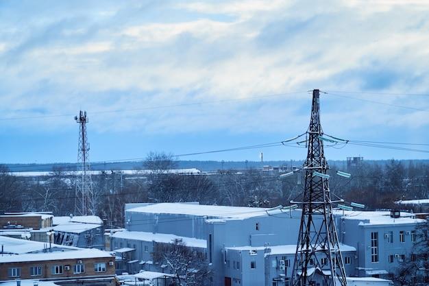 Torre della linea di trasmissione di potenza con isolanti ad alta tensione innevati. orario invernale