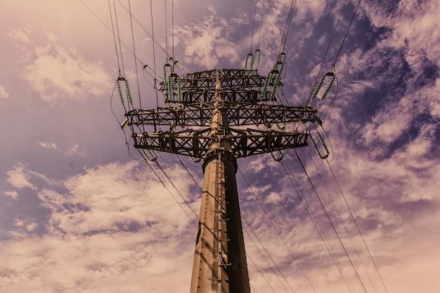 Torre della trasmissione (torre elettrica, pilone dell'elettricità, torre a traliccio in acciaio) al crepuscolo negli stati uniti. strutturi il pilastro ad alta tensione, la linea elettrica sopraelevata, fondo industriale. copia spazio