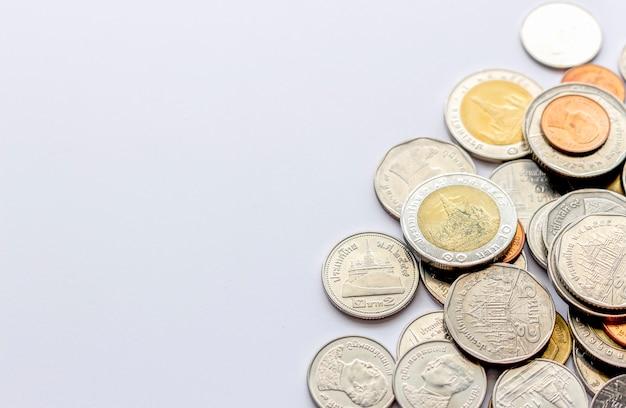Torre delle monete (soldi tailandesi) sulla tavola bianca con luce eccessiva e fuoco molle nei precedenti