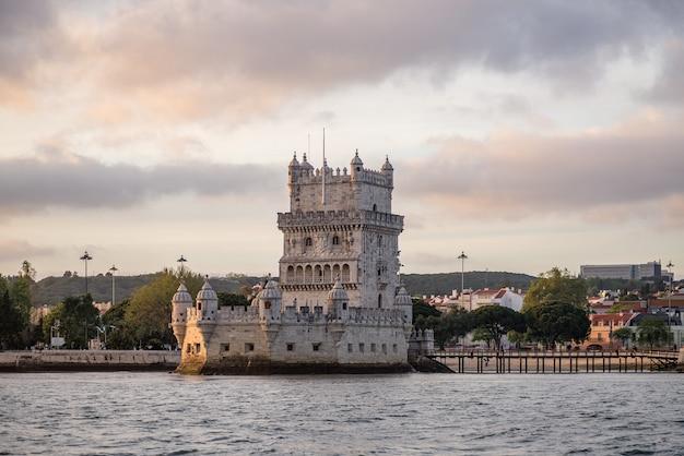 Torre di belem circondata dal mare e da edifici sotto un cielo nuvoloso in portogallo