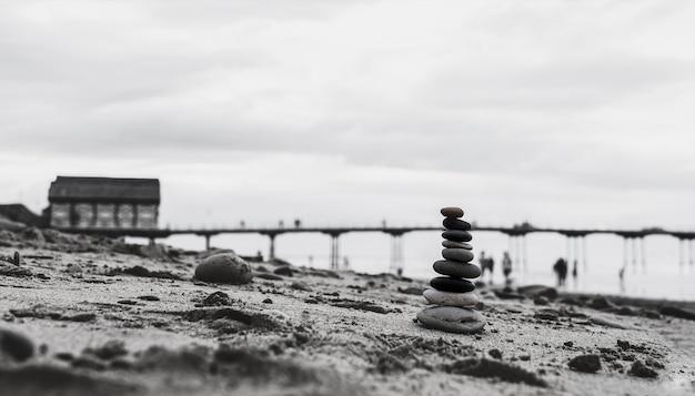 Torre di ciottoli in riva al mare con molo sfocato fino al mare